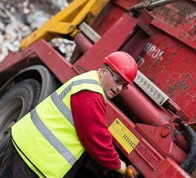 Ian Tyson operating a skip wagon.